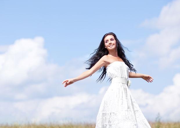 Mulher com vestido branco e expressão de felicidade