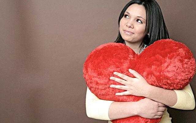 mulher abraçando um coração de pelúcia vermelho