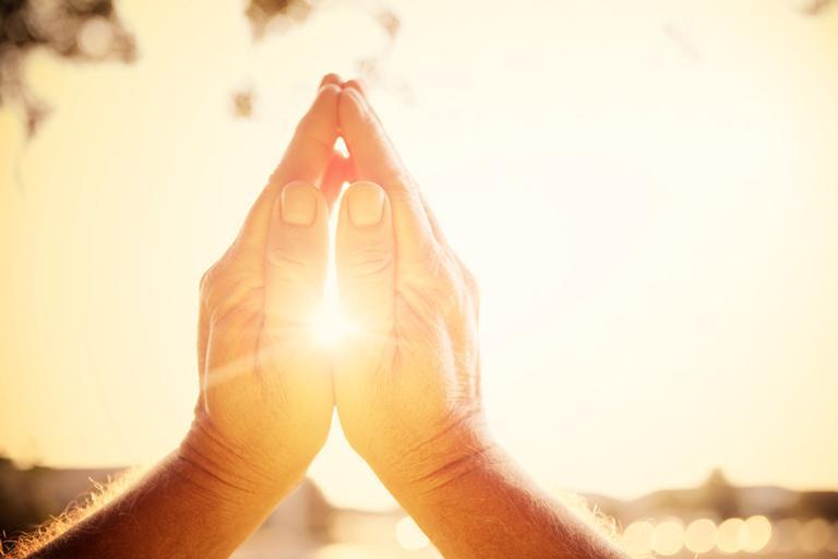 Mãos de uma pessoa rezando, representando séries de fé da Netflix.