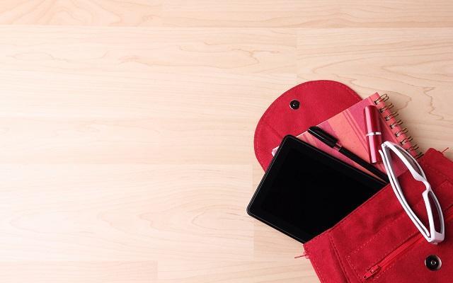 Mochila vermelha com cadernos e óculos para auxiliar nos estudos
