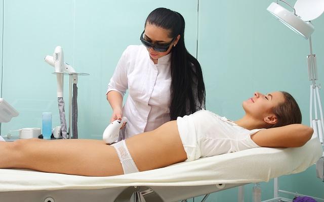 Na imagem, uma mulher está com roupa íntima, deitada na cama de estética com uma dermatologista fazendo depilação íntima na moça em uma clinica.