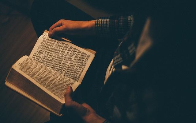 Pessoa lendo a bíblia em busca de salmos para elevar o astral