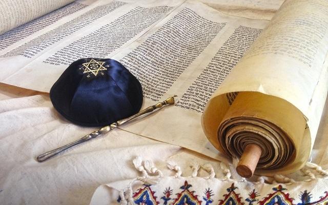 A foto mostra um manuscrito hebraíco, um kippah e um talith. Celebrações judaicas