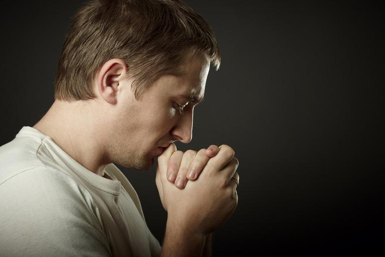 Homem de camiseta branca rezando orações para curar doenças