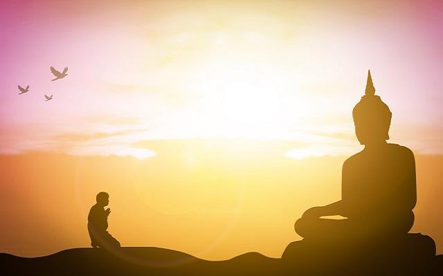 A foto mostra uma pessoa budista rezando em frente a uma estátua de Buda, representando a vida após a morte