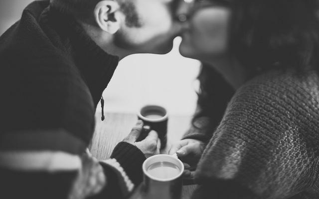 Na imagem, o casal beija apaixonadamente enquanto tomam café juntos. Beijo na boca.