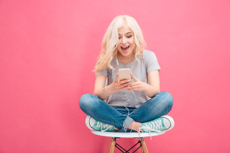 mulher loira com o cabelo longo solto sentada em um banco mexendo no celular para ilustrar a matéria da enquete do instagram de cada signo