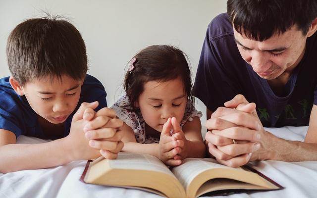 Família reunida rezando com a bíblia para ore com seus filhos
