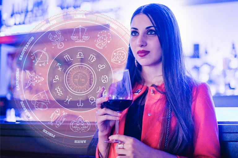 Foto de mulher morena em bar, com copo de vinho observando algo ou alguém, para ilustrar a matéria o lado bêbado de cada signo