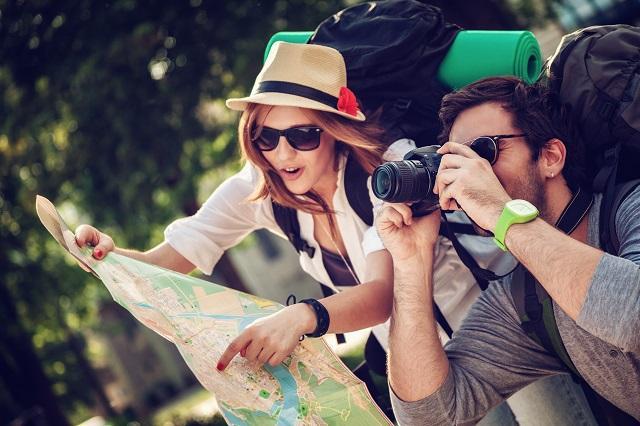 namorados viajantes com mapas e máquina fotográfica na mão para tirar fotos de lugares exuberantes. Imagem para ilustrar post sobre destinos românticos