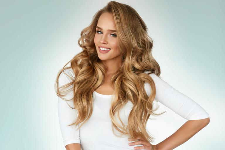 Mulher loira, de cabelos cacheados e ondulados, confiante e sedutora.