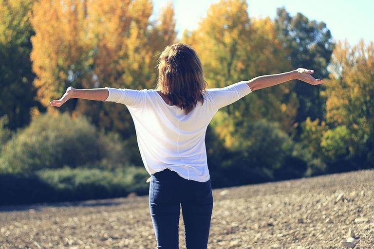 Mulher de braços abertos em campo feliz por sua limpeza astral