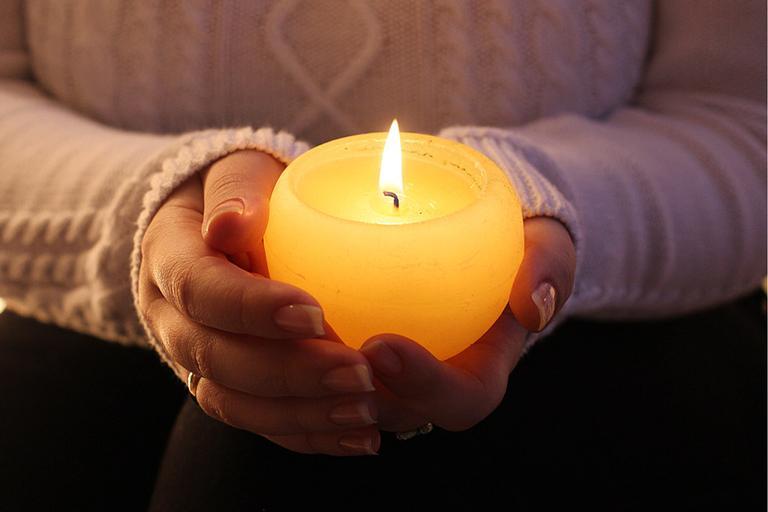 pessoa segurando uma vela branca acesa com as duas mãos