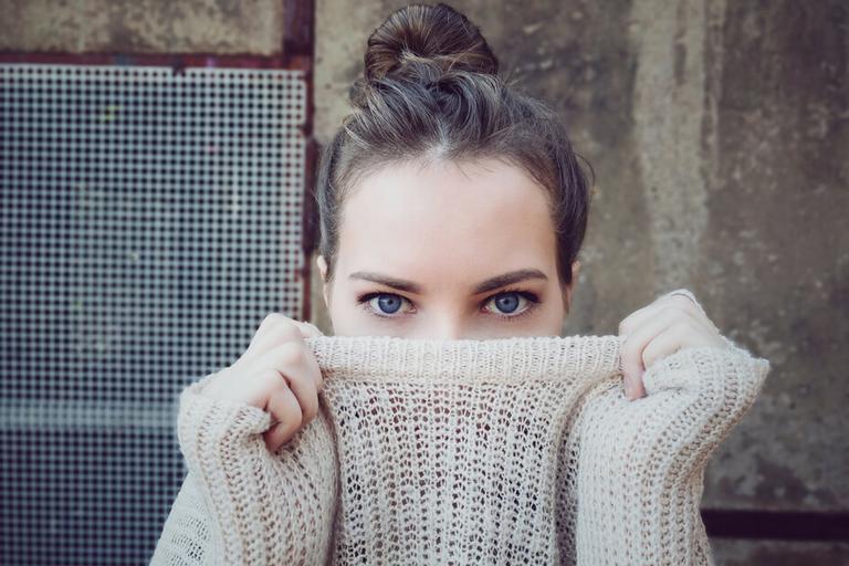Mulher com olhar preocupado cobrindo o rosto para que afaste a inveja e a falsidade