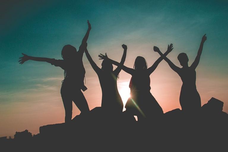 Na imagem, a silhueta de mulheres posam felizes. Cultura da menstruação.