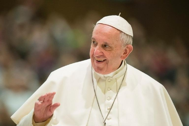 Na imagem, o papa francisco acena para o público sorrindo. Termo LGBT.