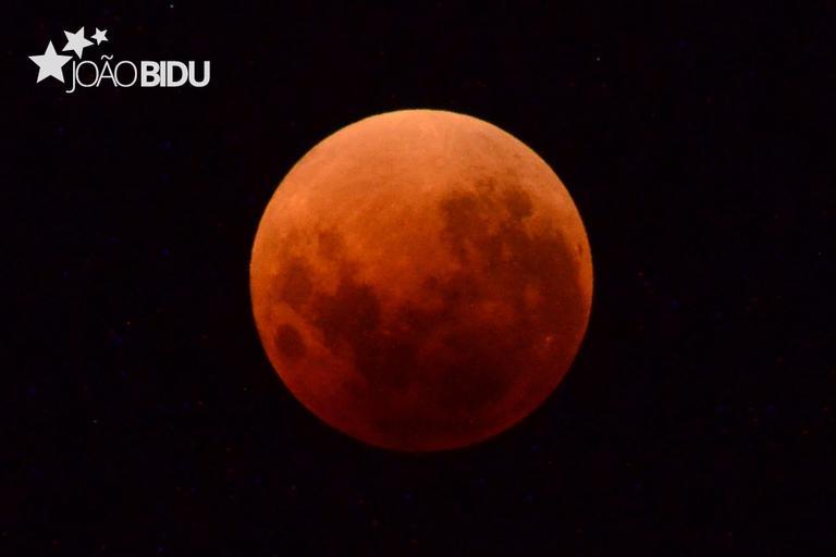 Lua de Sangue no centro da imagem e escrito João Bidu no canto superior esquerdo.