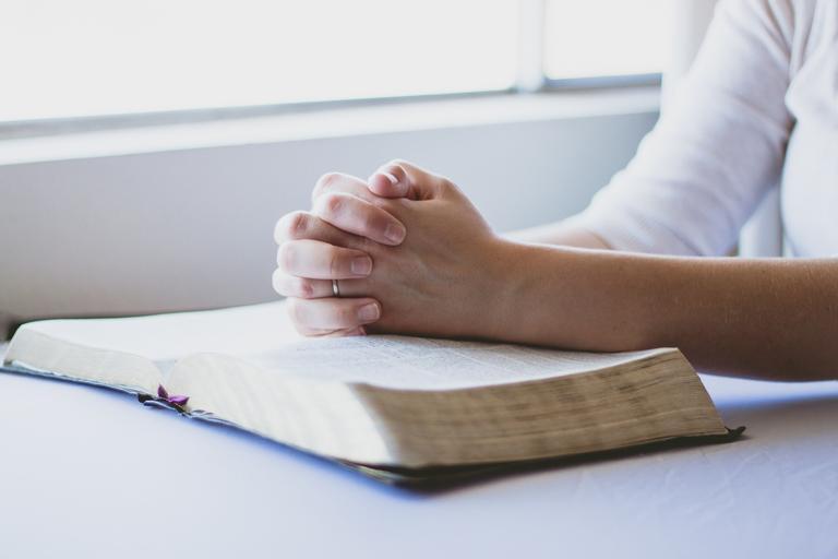 Mãos femininas em prece sobre a bíblia pedindo proteção espiritual