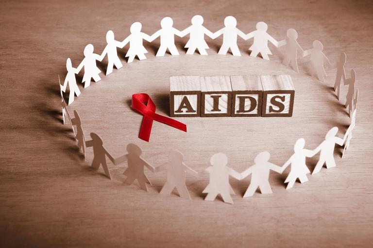 Na imagem, o sinal vermelho da aids está junto com as letras que escreve o nome da doença, em volta estão vários bonecos de papel juntos. HIV na adolescência.