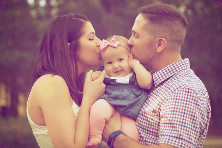 Casal beijando bebê em parque para uma família abençoada