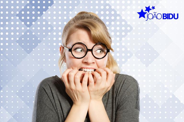 Mulher branca, loira, de óculos com as mãos na boca, demonstrando apreensão sobre fundo azul, com selo João Bidu no canto superior direito