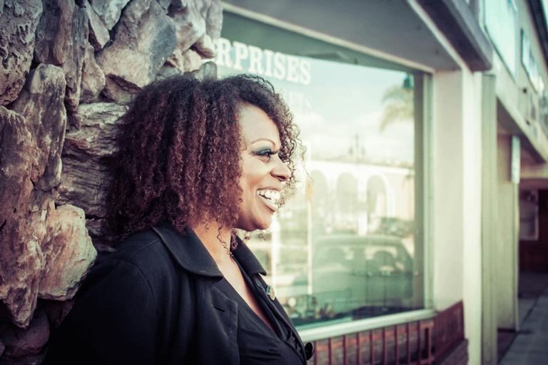 Mulher feliz em frente à loja para fazer para fazer a prosperidade reinar em sua vida