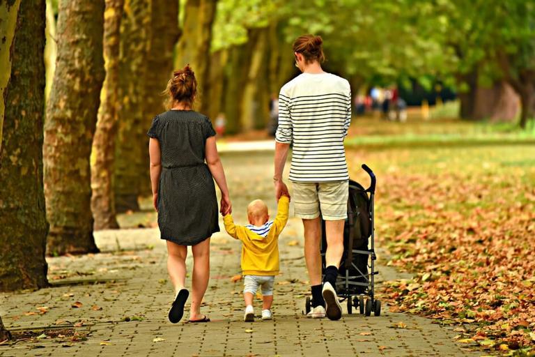 Casal caminha no parque com bebê e carrinho para orações para proteger a família