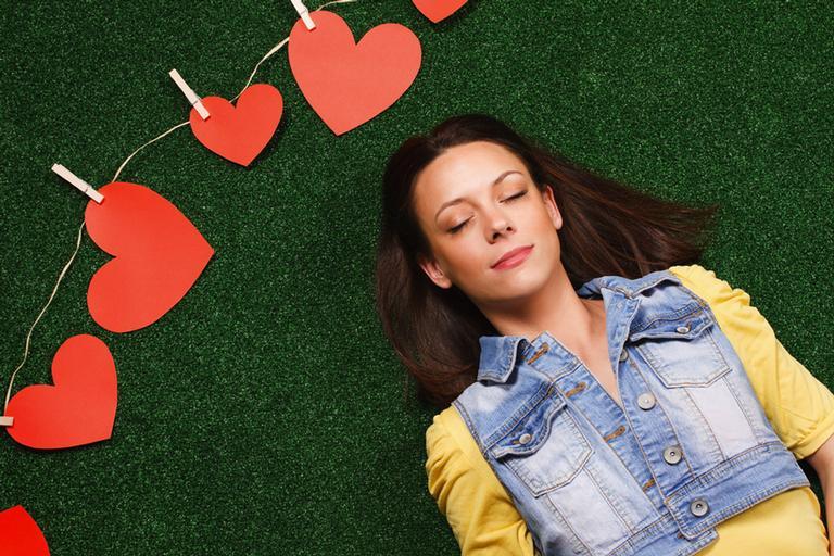 Mulher deitada em grama sintética, de olhos fechados, com um varal de corações de papel, perto da cabeça dela.