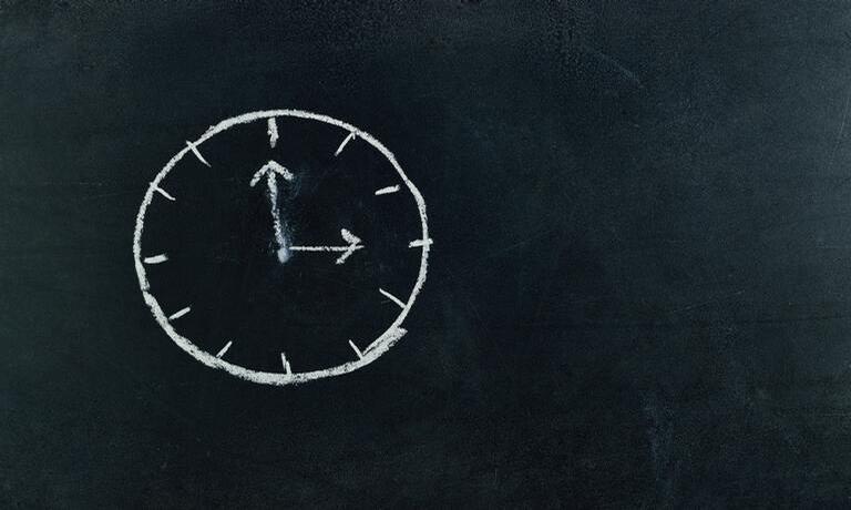 Relógio desenhado em giz em um quadro.